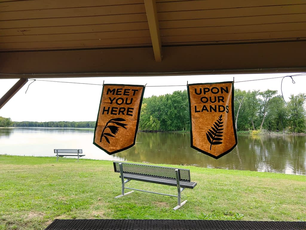 "A picnic shelter frames a view of a bench looking out on a river. Two tan and green cloth banners hang from the shelter reading ""Meet you here"" and ""Upon our lands"""
