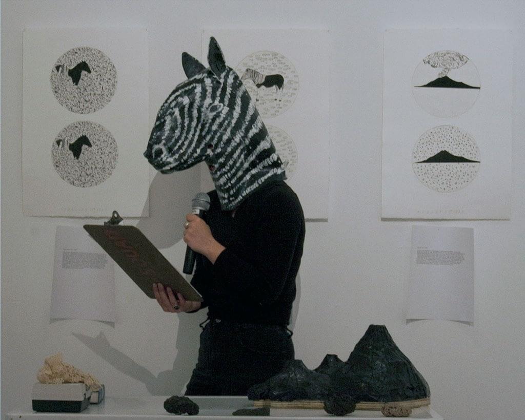 A performer reading from a clipboard wearing a papier mache a zebra head