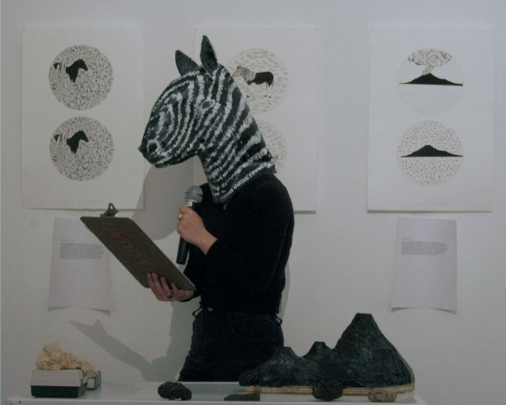 A performer reading from a clipboard wearing a papier mache a zebra head