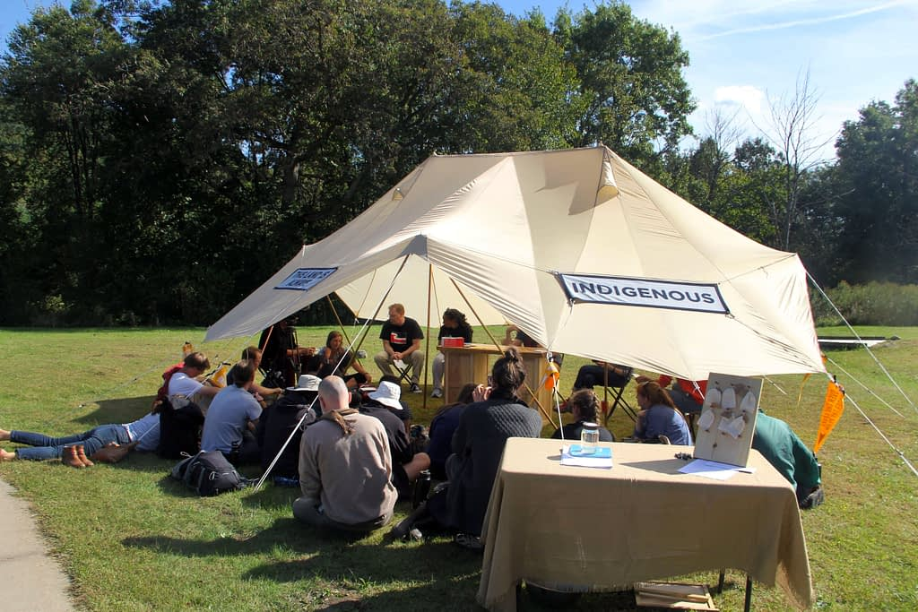 """A large group gathers under a shade tent for a discussion.The tent has a banner reading """"Indigenous"""""""