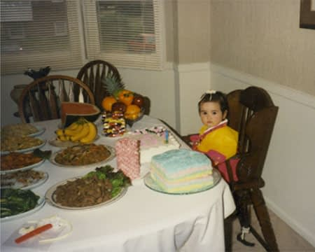 A toddler in traditional Korean dress sits alone at a table set for a birthday party