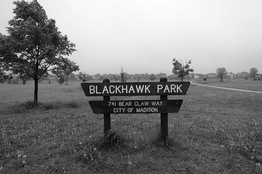 "Image of park sign reading ""Blackhawk Park"" in a mundane landscape"