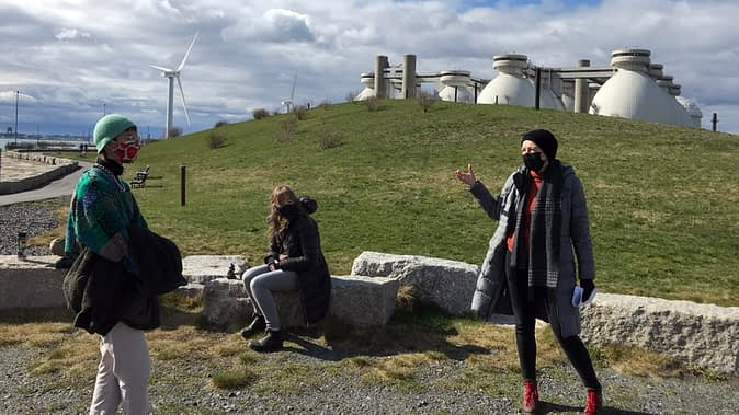 Three figures in PPE masks are arrayed in the foreground of a landfill hill with protruding monitoring pipes. One figure gestures and seems to be speaking. Industrial infrastructure can be viewed beyond the hill.