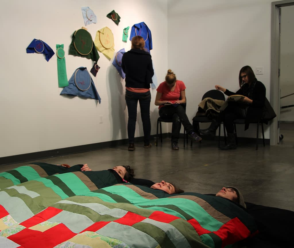 People lie on floor beneath brightly colored quilt while others touch cloth samples on the walls