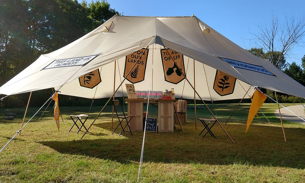 Open-sided tent with banners and a wooden tablee