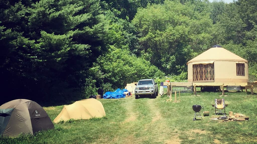 A clearing in the woods contains a yurt, truck, campfire, and two additional tents in the foreground.
