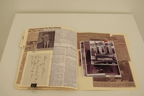A file folder with images and newspaper clippings