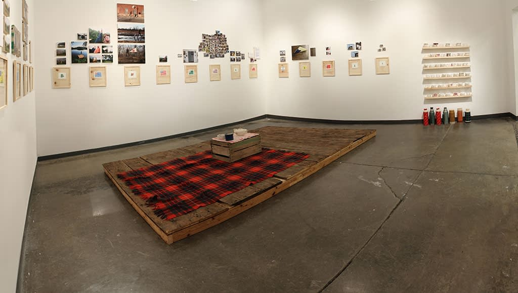 Gallery installation with small objectson wall and platform with plaid blanket on the floor
